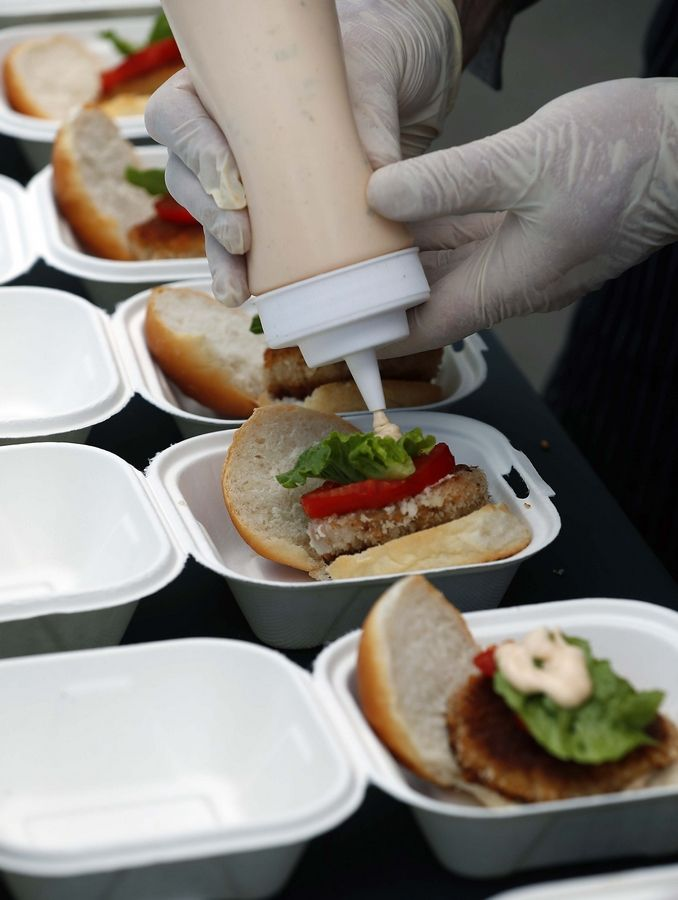 A Complete Culinary worker applies sauce to an Asian carp burger at a giveaway Friday in Aurora.