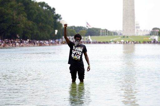 "A man stands in the Reflecting Pool as people attend the March on Washington, Friday Aug. 28, 2020, in Washington, on the 57th anniversary of the Rev. Martin Luther King Jr.'s ""I Have A Dream"" speech."