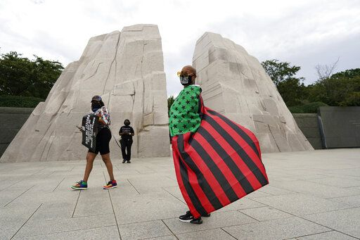 "Terri Biley, of Los Angeles, stands at The Martin Luther King, Jr. Memorial during the March on Washington, Friday Aug. 28, 2020, in Washington, on the 57th anniversary of the Rev. Martin Luther King Jr.'s ""I Have A Dream"" speech."