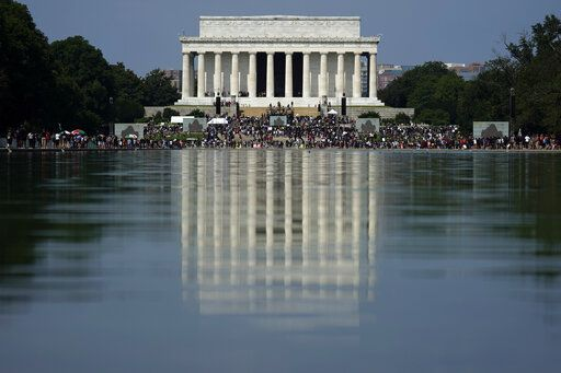 "The Lincoln Memorial is reflected in the water as people gather to attend the March on Washington, Friday Aug. 28, 2020, in Washington, on the 57th anniversary of the Rev. Martin Luther King Jr.'s ""I Have A Dream"" speech."