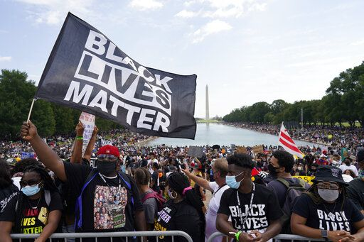 "People attend the March on Washington, Friday Aug. 28, 2020, in Washington, on the 57th anniversary of the Rev. Martin Luther King Jr.'s ""I Have A Dream"" speech."