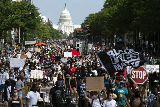 "People walk on Pennsylvania Avenue during the March on Washington, Friday Aug. 28, 2020, on the 57th anniversary of the Rev. Martin Luther King Jr.'s ""I Have A Dream"" speech."