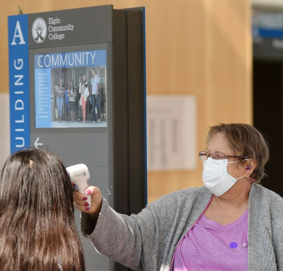 Healthcare screener Cynthia Ellis checks temperatures as people enter the building at Elgin Community College Wednesday.