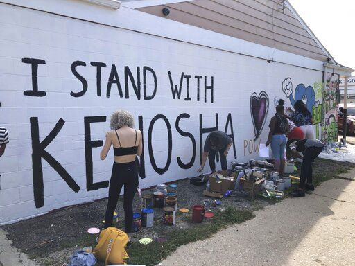 "Volunteers paint murals on boarded-up businesses in Kenosha, Wis., on Sunday, Aug. 30, 2020, at an ""Uptown Revival."" The event was meant to gather donations for Kenosha residents and help businesses hurt by violent protests that sparked fires across the city following the police shooting of Jacob Blake."