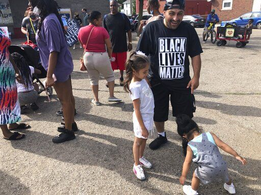 "Angel Crocket, 40, a Kenosha, Wis., resident, and immigrant from Guatemala, dance with his daughters, Yanira, 6, left and Noel, 2, right, on Sunday, Aug. 30, 2020, at an ""Uptown Revival."" The event was meant to gather donations for Kenosha residents and help businesses hurt by violent protests that sparked fires across the city following the police shooting of Jacob Blake."