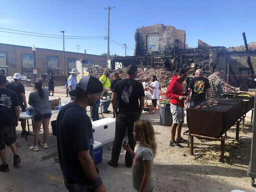 Volunteers prepare hamburgers for mural painting volunteers working in front of one of the city's dozens of burnt buildings in Kenosha, Wis., Sunday, Aug. 30, 2020. The southern Wisconsin city remained on edge following the police shooting of Jacob Blake, a Black man, and the violent protests that followed.