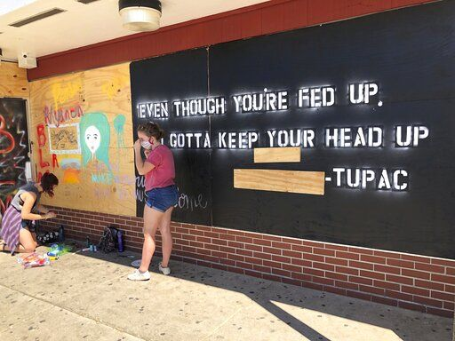 "Volunteers paint murals with lyrics from late hip-hop artist Tupac on boarded-up businesses in Kenosha, Wis., on Sunday, Aug. 30, 2020, at an ""Uptown Revival."" The event was meant to gather donations for Kenosha residents and help businesses hurt by violent protests that sparked fires across the city following the police shooting of Jacob Blake."