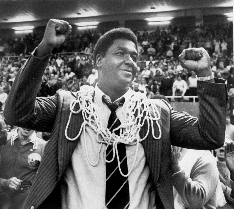 "FILE -- In this March 1, 1980, file photo, Georgetown University basketball coach John Thompson raises his hands in victory after fans placed the net around his neck in Providence, R.I., after Georgetown defeated Syracuse University 87-81 to win the Big East basketball championship. John Thompson, the imposing Hall of Famer who turned Georgetown into a ""Hoya Paranoia"" powerhouse and became the first Black coach to lead a team to the NCAA men's basketball championship, has died. He was 78 His death was announced in a family statement Monday., Aug. 31, 2020. No details were disclosed. (Anestis Diakopoulos/Providence Journal via AP, File)"