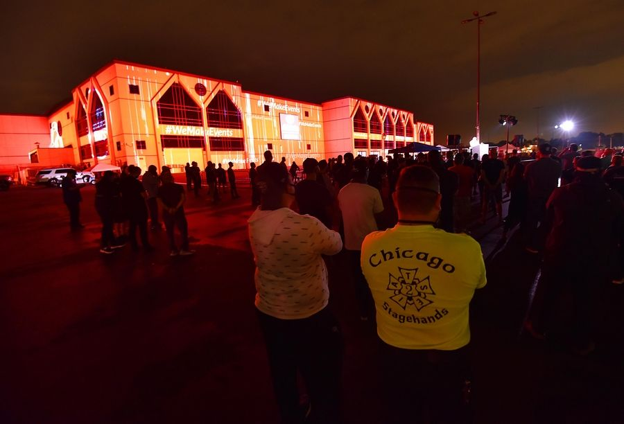 John Starks/jstarks@dailyherald.comA man wears a IATSE Labor Union t-shirt to represent theatrical stage employees as the Allstate Arena is lit with red lights Tuesday night to raise awareness of the COVID-19 devastation on the entertainment industry.