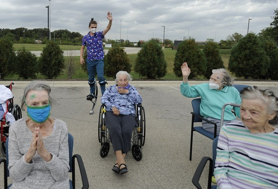 Socially distanced residents of Harvester Place memory care center were treated to a jumping springs circus act by Evan Baird of Downers Grove on Thursday.