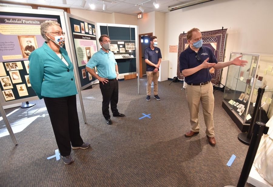 Cook County Board President Toni Preckwinkle, from left, Arlington Heights Mayor Tom Hayes, and Cook County Commissioner Kevin Morrison listen to Arlington Heights Historical Museum Administrator Dan Schoeneberg on a tour of the museum Saturday.