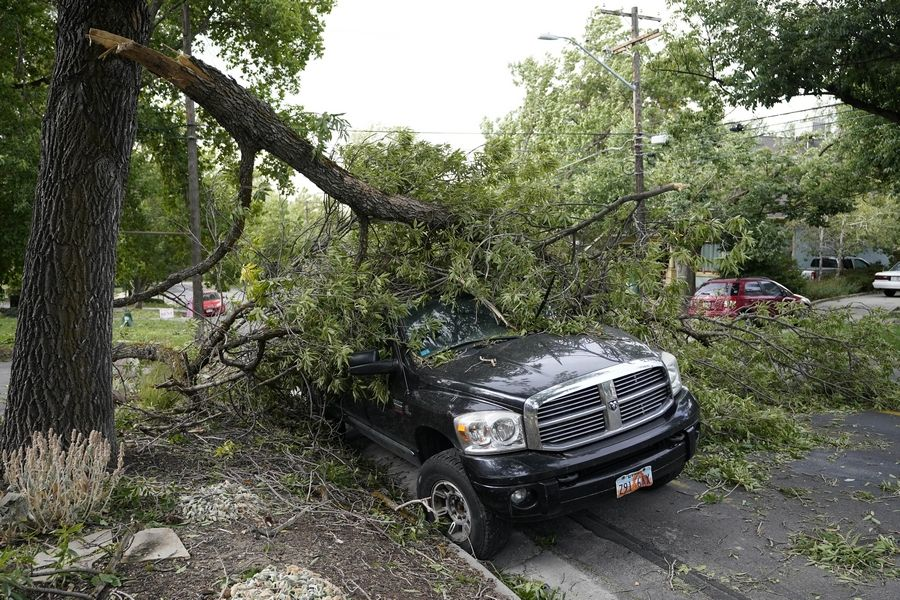 A tree limb rest on a vehicle after high winds caused widespread damage and power outages Tuesday, Sept. 8, 2020, in Salt Lake City.