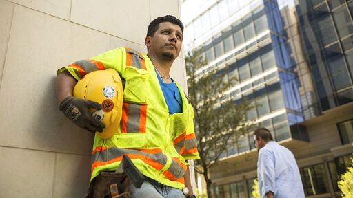 "This undated photo provided by Panda Bear Films/Latino Public Broadcasting shows Latino construction worker stands outside a Dallas construction site. ""Building the American Dream,"" a new VOCES/PBS documentary scheduled to air on most PBS stations on Tuesday, Sept. 15, 2020, examines the effects of this construction boom in the American Southwest on Latino workers by telling the stories of those erecting buildings in Texas. (Moyo Oyelola/Panda Bear Films/Latino Public Broadcasting via AP)"