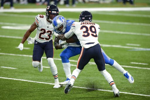 Detroit Lions running back Adrian Peterson (28) runs between Chicago Bears free safety Eddie Jackson (39) and cornerback Kyle Fuller (23) in the first half of an NFL football game in Detroit, Sunday, Sept. 13, 2020.