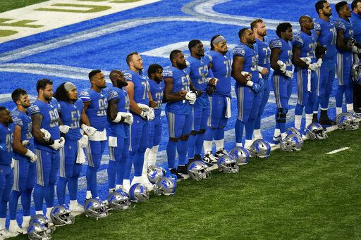 Detroit Lions players stand arm in arm during a social justice video before an NFL football game against the Chicago Bears in Detroit, Sunday, Sept. 13, 2020.