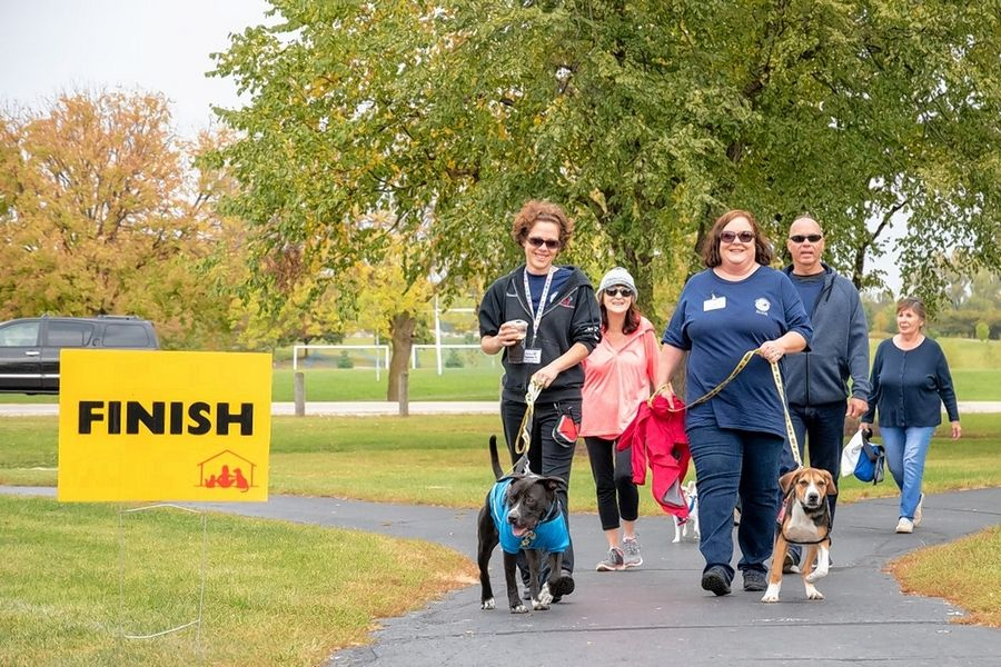 Walkers and their pets cross the finish line at a previous Barkapalooza fundraiser. This year's event features a variety of online activities.