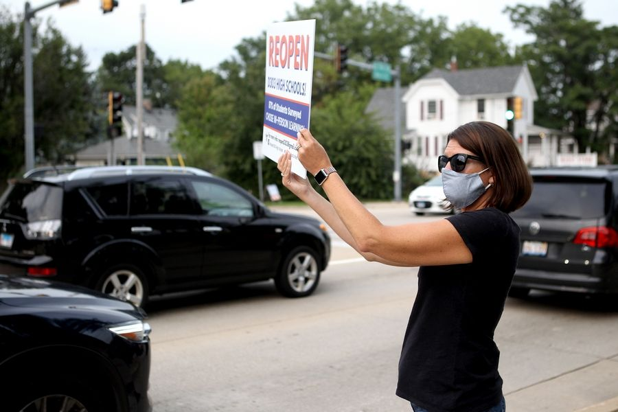 Colleen Deutmeyer, the parent of a St. Charles North freshman, holds a sign urging St. Charles Unit District 303 board members to reopen St. Charles East and North high schools outside Thompson Middle School in St. Charles before a board meeting later.