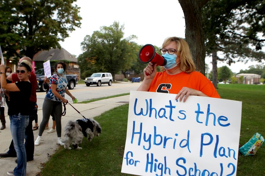 St. Charles North parent Shannon Sullivan leads the chanting during a rally urging St. Charles Unit District 303 board members to reopen St. Charles East and North high schools outside Thompson Middle School in St. Charles prior to a board meeting later.