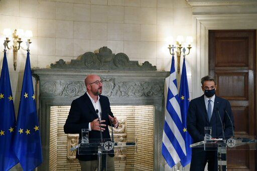 European Council President Charles Michel, left, makes statements after his meeting with Greece's Prime Minister Kyriakos Mitsotakis at Maximos Mansion in Athens, Tuesday, Sept. 15, 2020. Michel will visit Lesbos later today as Greece's migration minister says the government will use force if necessary to move homeless migrants to a new facility on the island after thousands of people were left without shelter by fires last week at an overcrowded refugee camp.