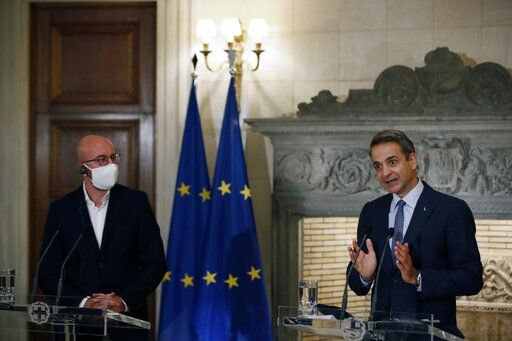 Greece's Prime Minister Kyriakos Mitsotakis, right, makes statements after his meeting with European Council President Charles Michel at Maximos Mansion in Athens, Tuesday, Sept. 15, 2020. Michel will visit Lesbos later today as Greece's migration minister says the government will use force if necessary to move homeless migrants to a new facility on the island after thousands of people were left without shelter by fires last week at an overcrowded refugee camp.