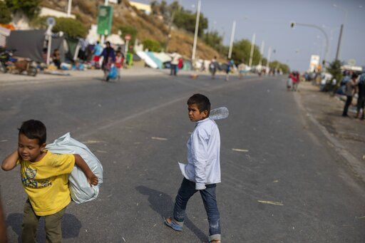 A boy carries a plastic bag as migrants gather on the roadside near Mytilene town, on the northeastern island of Lesbos, Greece, Tuesday, Sept. 15, 2020. Just over 6% of the 12,500 people left homeless last week by the fire that destroyed Greece's biggest camp for refugees and migrants have been rehoused in a new temporary facility under construction on the island of Lesbos.