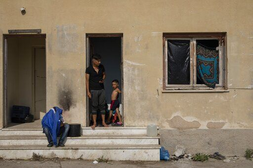 Migrants gather at an abandoned building near Mytilene town, on the northeastern island of Lesbos, Greece, Tuesday, Sept. 15, 2020. Just over 6% of the 12,500 people left homeless last week by the fire that destroyed Greece's biggest camp for refugees and migrants have been rehoused in a new temporary facility under construction on the island of Lesbos.