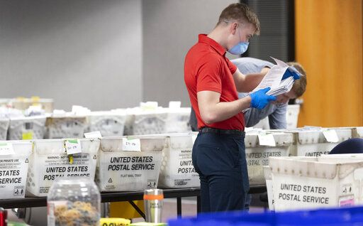 FILE - In this April 8, 2020 file photo, a City of Milwaukee Election Commission worker processes and sorts absentee ballots for Wisconsin's primary election, in downtown Milwaukee, Wis. Election clerks across the presidential battleground state of Wisconsin rushed to mail absentee ballots Tuesday, Sept. 15, 2020, less than 24 hours after the state Supreme Court lifted a temporary freeze on sending them while it considered a legal challenge. (Mark Hoffman/Milwaukee Journal-Sentinel via AP, File)