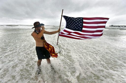 Corbin Boyce holds an American flag on the beach near Fort Walton Beach, Fla., on Tuesday, Sept. 15, 2020, as strong winds and rough waves from Hurricane Sally scour the shoreline. (Devon Ravine/Northwest Florida Daily News via AP)