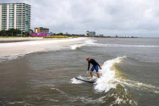 Bryan Lockwood, of Gulfport, takes advantage of the waves being brought into the Mississippi Sound in Biloxi, Miss. from Hurricane Sally to surf, Tuesday, Sept. 15, 2020. Hurricane Sally is still moving slowly towards the Gulf Coast, and is expected to bring between 10 to 20 inches of rainfall to a number of communities along the waters. (Lukas Flippo/The Sun Herald via AP)