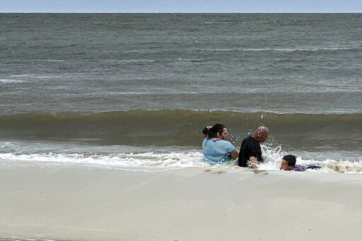 A family enjoys the warm waters of the Gulf of Mexico as they play in the surf at this west Gulfport, Miss., beach, ahead of landfall of Hurricane Sally, Tuesday, Sept. 15, 2020. Hurricane Sally is still moving slowly toward the Gulf Coast, and is expected to bring between 10 to 20 inches of rainfall.  (Hunter Dawkins/The Gazebo Gazette via AP)