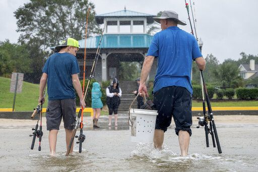 A father and son walk through the Hurricane Sally tidal surge in Ocean Springs, Miss., to fish on the beach, Tuesday, Sept. 15, 2020. Hurricane Sally slowly approaches the Gulf Coast Tuesday evening, and is expected to bring between 10 to 20 inches of rainfall. (Lukas Flippo/The Sun Herald via AP)