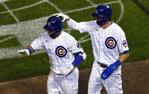 Chicago Cubs' Kris Bryant, right, pats Willson Contreras, left, on the helmet after Contreras drove in Bryant on a RBI sacrifice fly against the Cleveland Indians during the seventh inning of a baseball game, Tuesday, Sept.15, 2020, in Chicago.