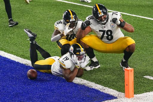 Pittsburgh Steelers wide receiver JuJu Smith-Schuster (19) offensive tackle Alejandro Villanueva (78) and wide receiver Diontae Johnson (18) celebrate after Smith-Schuster scored a touchdown against the New York Giants during the fourth quarter of an NFL football game Monday, Sept. 14, 2020, in East Rutherford, N.J.