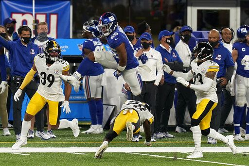 New York Giants running back Saquon Barkley (26) leaps over Pittsburgh Steelers cornerback Mike Hilton (28) during the second quarter of an NFL football game Monday, Sept. 14, 2020, in East Rutherford, N.J.