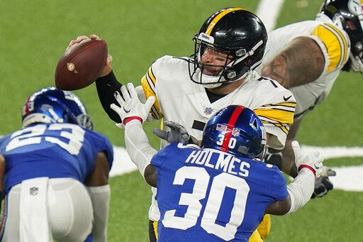 Pittsburgh Steelers quarterback Ben Roethlisberger (7) looks to pass under pressure from New York Giants cornerback Darnay Holmes (30) during the first quarter of an NFL football game Monday, Sept. 14, 2020, in East Rutherford, N.J.