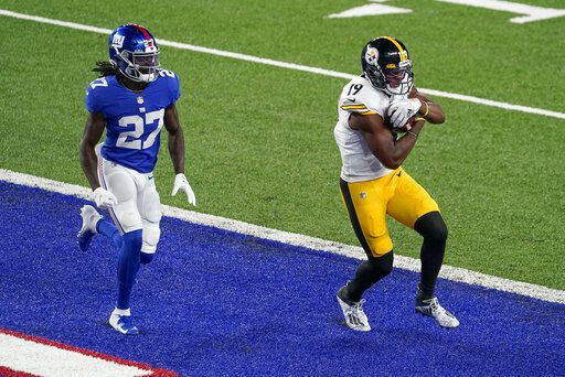 Pittsburgh Steelers wide receiver JuJu Smith-Schuster (19) comes down with a touchdown pass in front of New York Giants cornerback Isaac Yiadom (27) during the second quarter of an NFL football game Monday, Sept. 14, 2020, in East Rutherford, N.J.