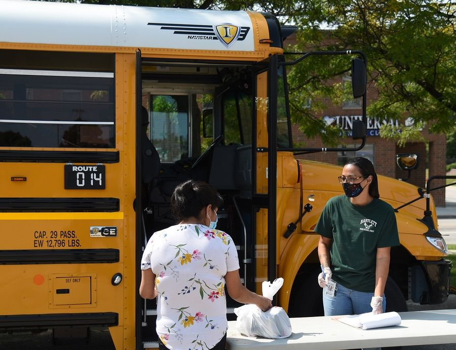 Claudia Orduno, a food services technician at Bartlett High School, passes out the last two lunches to a woman at an Elgin Area School District U-46 food distribution site at Raymond and National streets in Elgin Wednesday.