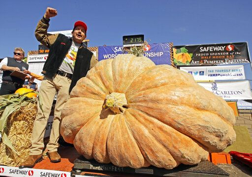 FILE - Leonardo Urena of Napa, Calif., reacts after learning his pumpkin weighed in at 2,175 lbs., a new California weight record on Oct. 14, 2019, in Half Moon Bay, Calif. The Half Moon Bay Art & Pumpkin Festival, now canceled, usually draws up to 300,000 people from around the world. The kick-off event the week before, the World Championship Giant Pumpkin Weigh-Off, will carry on with no public spectators but plenty of humongous orange contestants as the judging goes virtual.