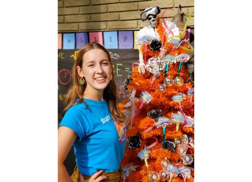 This mage released by Zolli Candy shows 15-year-old candy entrepreneur Alina Morse posing next to a decorated tree for Halloween. The family holiday so many look forward to each year is going to look different in the pandemic as parents and the people who provide Halloween fun navigate a myriad of restrictions and safety concerns. Morse suggests fashioning a Halloween candy tree decorated with lights and treats so kids can pluck their own from a porch or yard. (Klint Briney/Zolli Candy via AP)