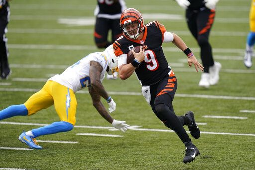 Cincinnati Bengals quarterback Joe Burrow (9) runs past Los Angeles Chargers' Rayshawn Jenkins (23) for a touchdown during the first half of an NFL football game, Sunday, Sept. 13, 2020, in Cincinnati.