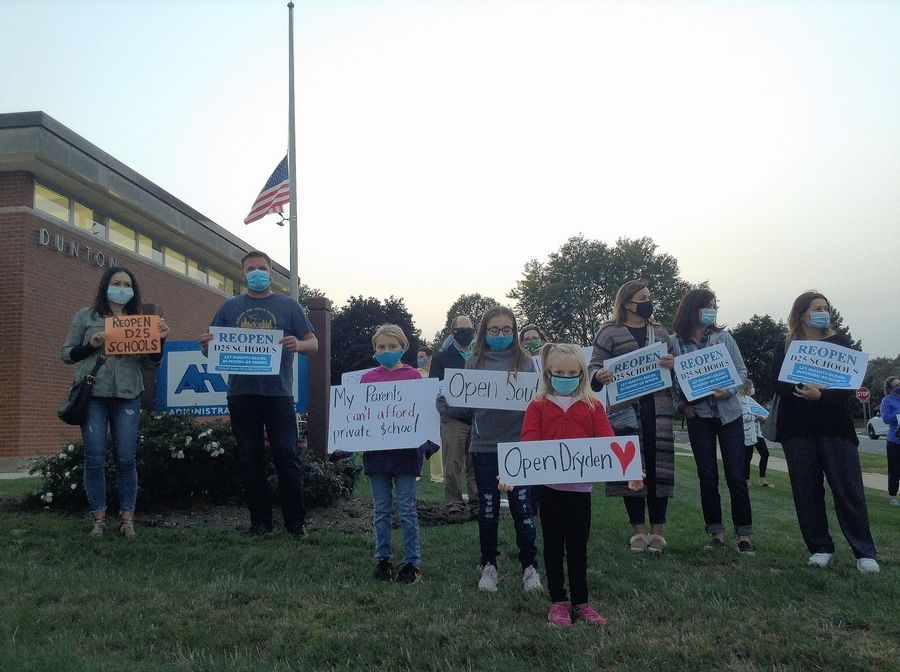 About 50 parents and students rallied outside the Arlington Heights Elementary District 25 Dunton Administration Building Thursday night before a school board meeting. They called for a return to in-person learning in lieu of the current remote model.