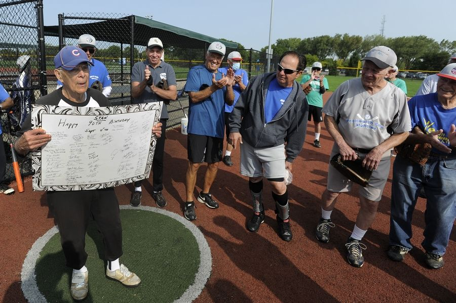 Holding a giant birthday card signed by his fellow players, Stanley Rauch celebrates by playing his first softball game since he turned 90 years old. The Schaumburg man is in his 41st season playing in the senior league.