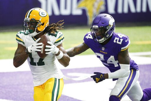 Green Bay Packers wide receiver Davante Adams catches a 1-yard touchdown pass ahead of Minnesota Vikings defensive back Holton Hill, right, during the second half of an NFL football game, Sunday, Sept. 13, 2020, in Minneapolis.