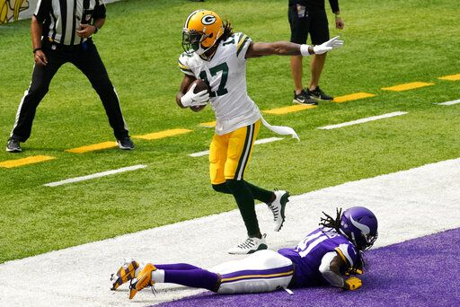 Green Bay Packers wide receiver Davante Adams (17) catches a 24-yard touchdown pass over Minnesota Vikings defensive back Anthony Harris during the first half of an NFL football game, Sunday, Sept. 13, 2020, in Minneapolis.