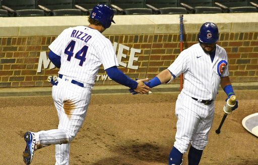 Chicago Cubs' Anthony Rizzo (44) is greeted by Kyle Schwarber (12) after scoring against the Minnesota Twins during the first inning of a baseball game, Friday, Sept. 18, 2020, in Chicago.