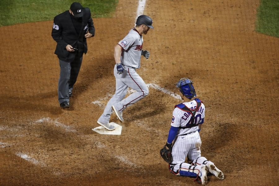 Minnesota Twins' Josh Donaldson, center, crosses home plate after hitting a solo home run off Chicago Cubs relief pitcher Dan Winkler during the ninth inning of a baseball game, Saturday, Sept. 19, 2020, in Chicago.