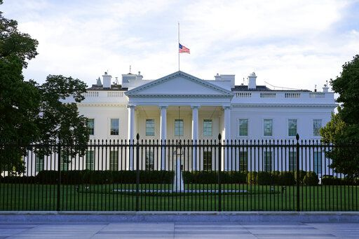 FILE - In this Saturday, Sept. 19, 2020, file photo, an American flag flies at half-staff over the White House in Washington. A woman suspected of sending an envelope containing the poison ricin, which was addressed to White House, has been arrested at the New York-Canada border.