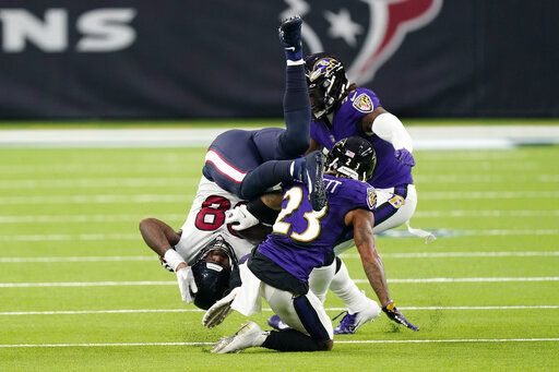 Houston Texans tight end Jordan Akins (88) is upended by Baltimore Ravens cornerback Anthony Averett (23) after making a catch during the second half of an NFL football game Sunday, Sept. 20, 2020, in Houston.