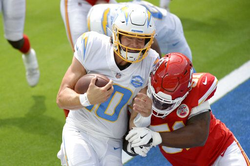 Los Angeles Chargers quarterback Justin Herbert runs into the end zone for a touchdown next to Kansas City Chiefs defensive end Michael Danna during the first half of an NFL football game Sunday, Sept. 20, 2020, in Inglewood, Calif.