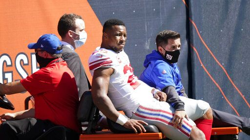 New York Giants running back Saquon Barkley (26) is carted to the locker room after being injured during the first half of an NFL football game against the Chicago Bears in Chicago, Sunday, Sept. 20, 2020.